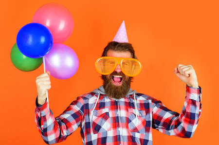 Party time. Joy, fun and happiness concept. Happy Man with balloons. Bearded man in party cap and big glasses. 版權商用圖片