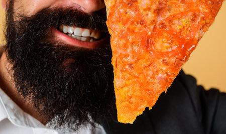 Pizzeria. Bearded man with slice of pizza. Italian cuisine. Delicious fast food. 版權商用圖片