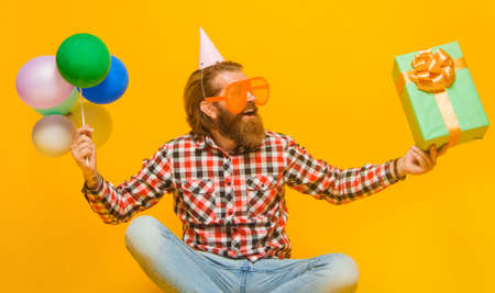 Party time. Happy Bearded man with present and balloons. Holidays and celebration.