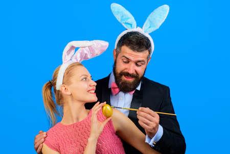 Bunny couple. Easter family painting eggs. Happy couple with rabbit ears. 版權商用圖片
