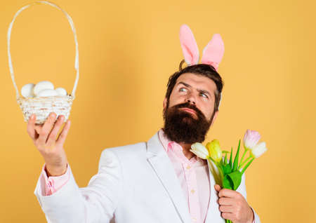 Easter Day. Egg hunt. Bearded man in bunny ears with basket eggs. Rabbit Man with bouquet of tulips.