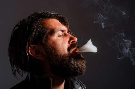 Man smoking cigarette. Brutal bearded male with cigarette. Cigarette smoke. Tobacco.