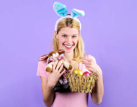 Easter Day. Smiling girl in rabbit ears with basket eggs and bunny toy.