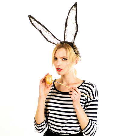 Sexy Woman Painting egg. Egg hunt. Easter girl in Bunny mask with Colored eggs.