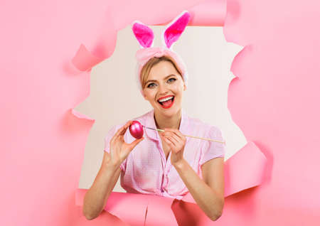 Happy bunny woman painting egg. Easter eggs ideas. Rabbit Woman looking through paper.