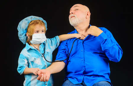 Child with Stethoscope play doctor with grandpa. Kid boy doctor playing with grandfather. Boy in doctor mask. Treatment.