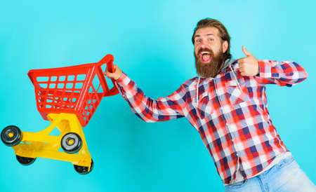 Supermarket. Bearded man running with empty shopping cart. Buying spree.