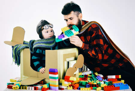 Family and childhood concept. Son and dad play with colorful plastic blocks. Father and child spend time together.