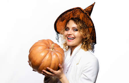 Halloween Witch with pumpkin. Smiling woman in witches costume. Halloween party girl. Carved Pumpkins. Standard-Bild