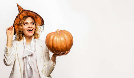 Happy Halloween. Smiling woman in witch hat with halloween pumpkin. Trick or treat. Copy space for Advertising. Standard-Bild
