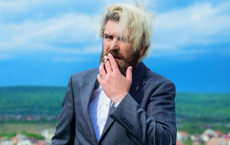 Businessman in suit smoke cigarette. Smoking man. Stylish bearded man with cigarette.