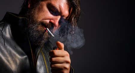 Smoking man. Bearded man lights cigarette. Bad habits. Fashionable guy smoke cigarette. Closeup.