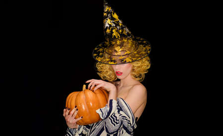 Halloween Party. Sensual girl with big pumpkin. Sexy woman in Witch hat with Jack-o-lantern.