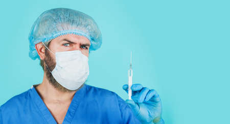 COVID-19 vaccination. Doctor in medical cap, mask, gown and gloves with syringe. Injection. Pandemic. Health care. Copy space.