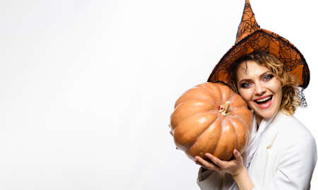 Girl witch with Pumpkin. Happy Halloween party. Smiling Woman with orange pumpkin. Traditional food. Copy space.