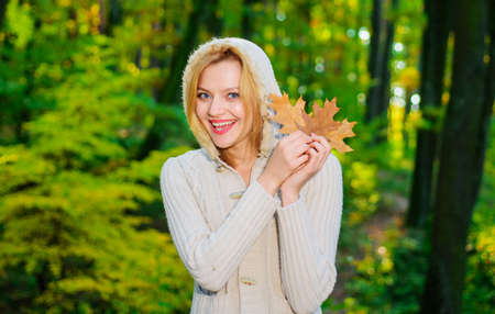 Autumn woman in autumn park. Warm sunny weather. Happy girl playing with yellow leaves. Female autumn fashion. Standard-Bild