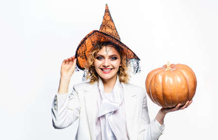 Halloween party. Wizard girl in witch hat with pumpkin. Autumn holiday. 31 October.