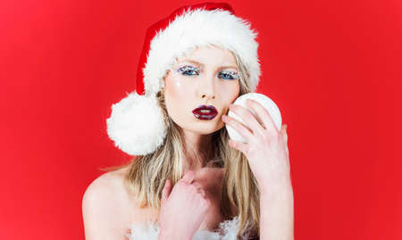 Sensual Woman in santa hat with Christmas tree ball. Christmas time and New year celebrating. Winter holidays.