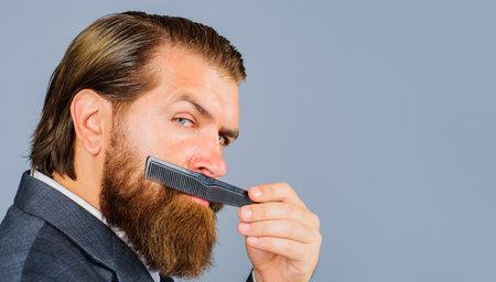 Bearded man with barber comb. Barbershop. Professional beard care. Hairdresser. Salon for men. Copy space for Barber-shop advertising. Standard-Bild