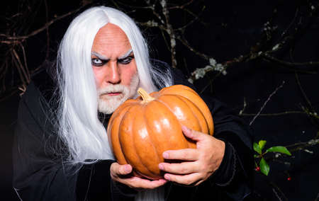 Devil man with pumpkin. Halloween night. Angry Man in witch costume with Jack-o-lantern. Happy Halloween.