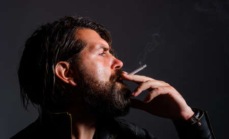 Bearded Man smoke cigarette. Fashionable guy in leather jacket with cigarette. Smoking hipster. Standard-Bild