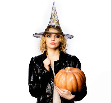 Happy Halloween. Sexy Girl witch with Pumpkin. Traditional food. Serious woman in witches hat and costume with orange pumpkin.