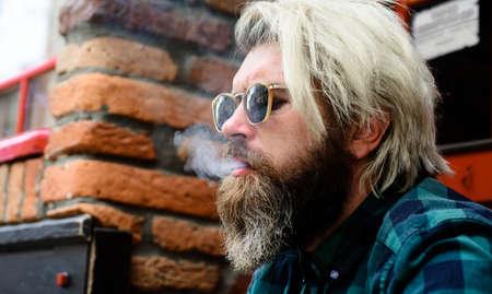 Smoking male. Bearded man smoke cigarette. Closeup Portrait. Handsome man smoking outside.