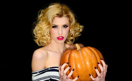 Halloween holidays. Sexy Witch with pumpkin. Sensual girl with jack-o-lantern. Magic Pumpkins. Traditional food. Standard-Bild