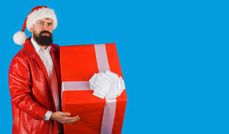 Santa Claus with present. Christmas time. Bearded man in Santa hat with gift box. New year advertising. Copy space.