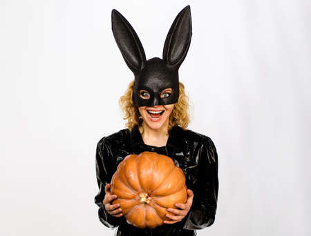 Beautiful girl in halloween bunny costume with pumpkin. Sexy blonde woman in rabbit black mask with jack-o-lantern. Standard-Bild