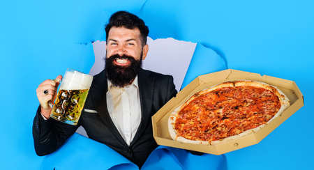 Bearded man with tasty pizza and beer looking through paper hole. Enjoy delicious pizza and cold beer. Standard-Bild