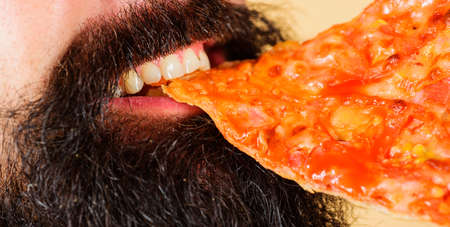 Pizzeria. Bearded man eat slice of pizza. Closeup. Italian cuisine. Tasty pizza at restaurant. Lunch or dinner. Standard-Bild