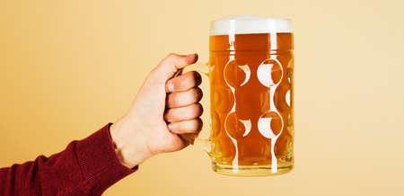 Oktoberfest. Man hand with glass of draft beer with foam. Fresh cold beer in glass in hand. Beer pub. Standard-Bild