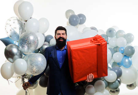 Smiling businessman with helium balloons and big present box. Bearded man with gift. Birthday, holidays, celebration.