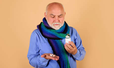 Bearded man with pills in hand. Male with bottle of medicine pill. Sick man taking tablet. Standard-Bild
