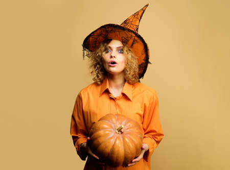 Surprised woman in witch hat with pumpkin. Girl in halloween costume with jack-o-lantern. Halloween holidays.