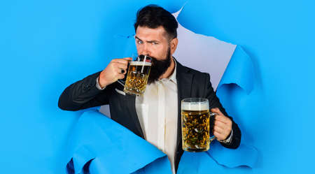 Bearded man with two mugs of beer looking through paper hole. Stylish male drinking beer. Lager and dark. Oktoberfest.