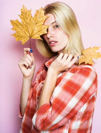 Sensual woman in casual wear with yellow leaves. Blonde girl with golden maple leafs. Autumn fashion. Autumn sales. Standard-Bild