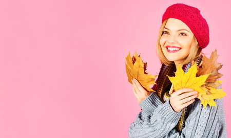 Smiling woman in warm sweater, scarf and hat with Autumn leaves. Discount and Season sale. Black friday. Copy space. Standard-Bild