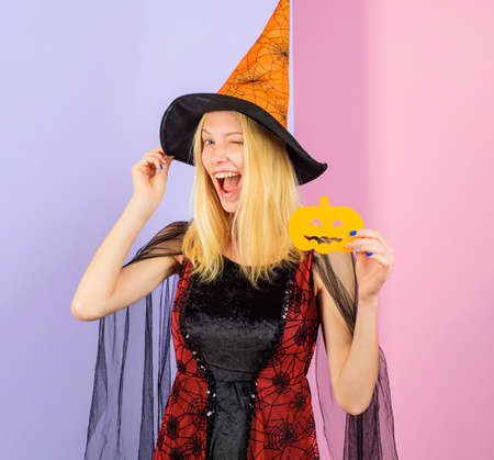 Smiling Witch with paper carved Pumpkin. Winking girl in witches hat and Halloween costume. Carving Pumpkin. 31 October. Standard-Bild