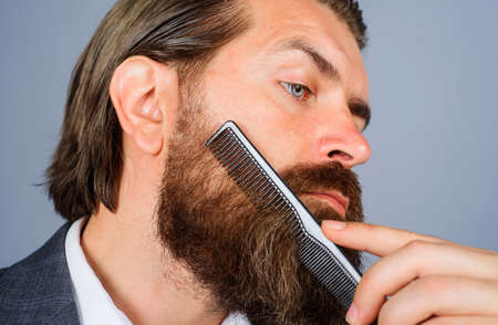 Barbershop. Bearded man with comb. Professional beard care. Handsome male with barber tools. Closeup.