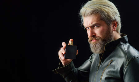 Mens cosmetics. Bearded man with Perfume or cologne bottle. Male fragrance and perfumery. Copy space.