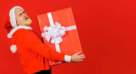 Delivery service. Santa Claus with Christmas gift. Bearded man in Santa hat with present box. Copy space.