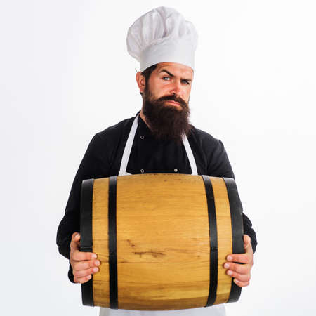 Male Chef with Wooden barrel with beer. Oktoberfest. Bearded man carry wooden barrel with wine. Homemade wine. Standard-Bild