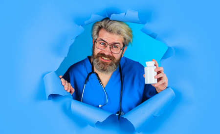 Doctor with pills looking through paper hole. Pharmaceutical drug. Male Nurse with stethoscope with Bottle of pills. Pharmacy concept. Standard-Bild