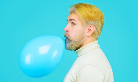 Preparation to party. Bearded man blowing balloon. Happy birthday. Holidays, celebration and lifestyle concept.