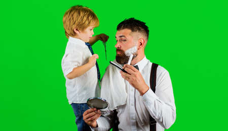Barbershop advertising. Son and Father in barbershop. Assistant for dad. Fathers day. Shaving in barber-shop. Standard-Bild