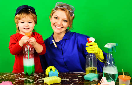 Happy Family. Cleaning time. Mother and son with cleaning supplies. Smiling woman and kid having fun during cleaning. Standard-Bild