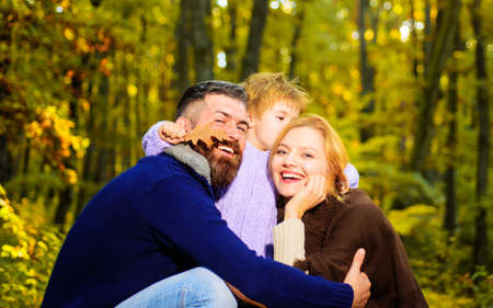 Happy family. Mother, father and little son together in park. Autumn nature. Smiling Autumn couple.