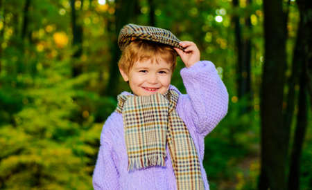 Smiling boy in sweater, hat and scarf. Little kid in Autumn park. Cute child in warm clothes.